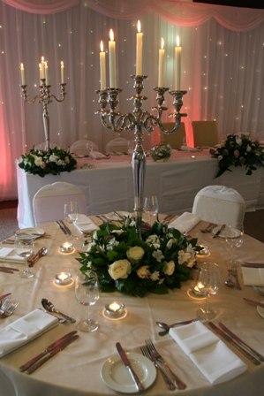 Clumber Park Hotel with silver candelabras, twinkle backdrop, white chair covers with champagne and baby pink sashes and table overlays.