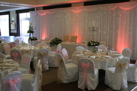 Clumber Park Hotel with white chair covers champagne and baby pink sashes finished with white twinkle backdrop and pink uplighters