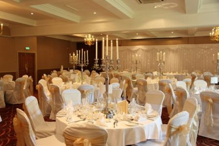 Candelabra with white chair covers and gold organza sashes