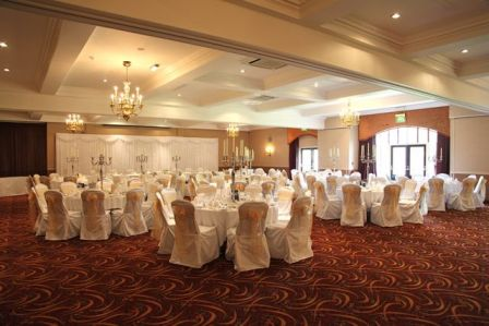 Twinkle backdrop with white chair covers and gold organza sashes at Tankersley Manor Hotel