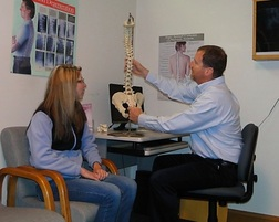 Chiropractor talks with patient